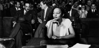 Woman sitting at table with people sitting behind her (© Griff Davis)