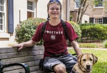 Young man seated on bench, with dog (Courtesy of University of South Carolina)