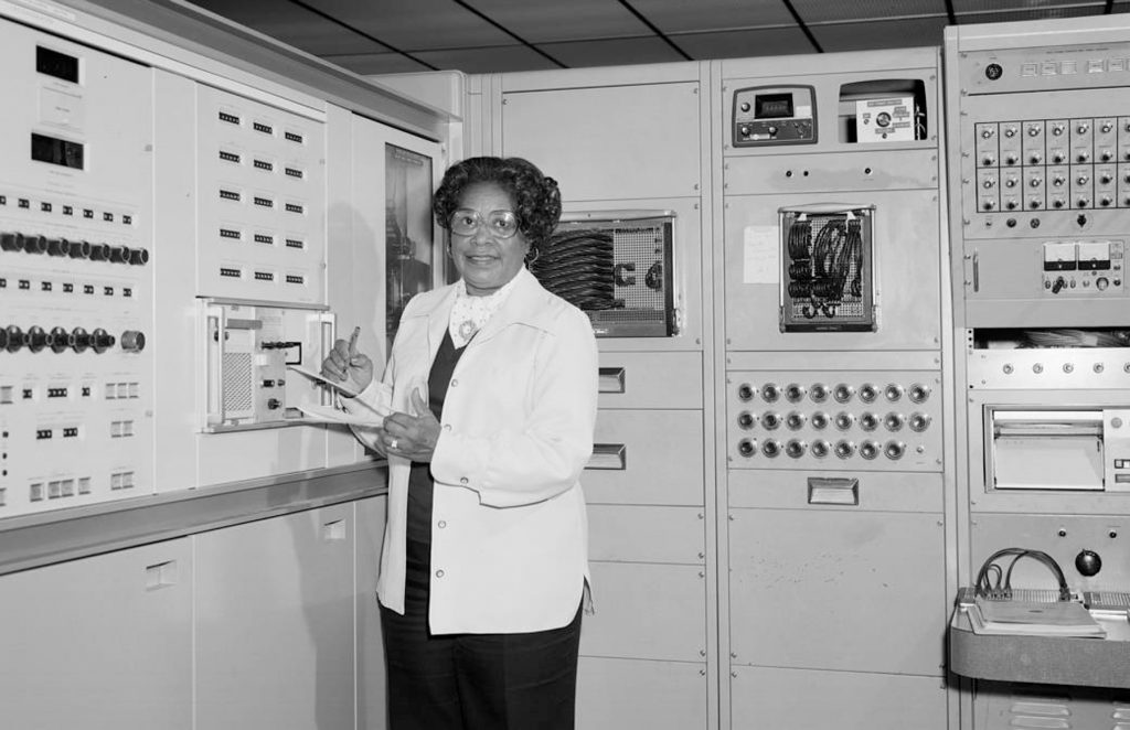Mary Jackson with pen in hand in room filled with machinery (NASA)