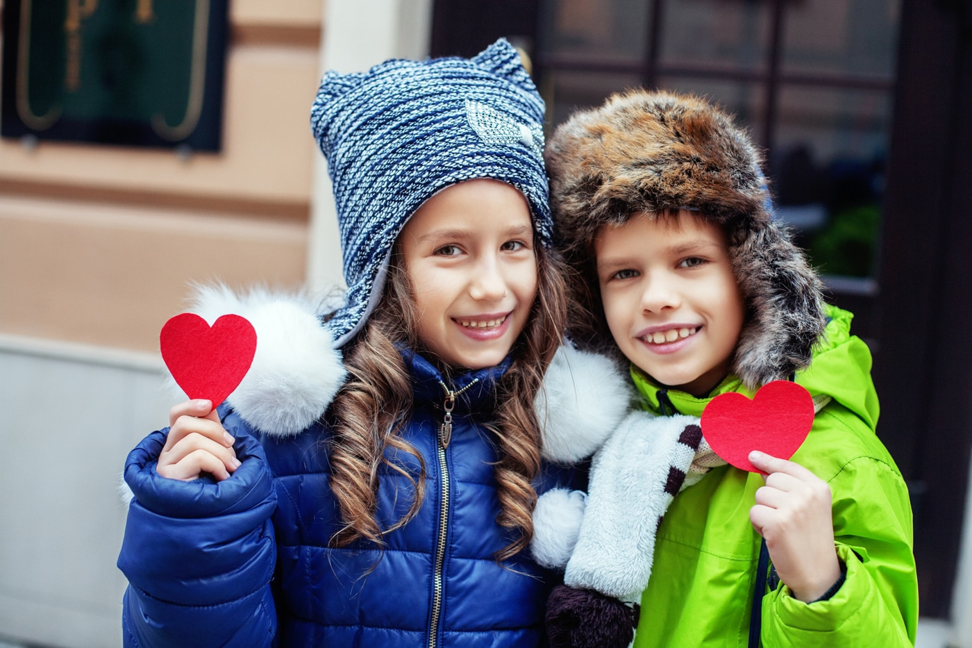 Two children smiling and holding paper hearts (© Shutterstock)