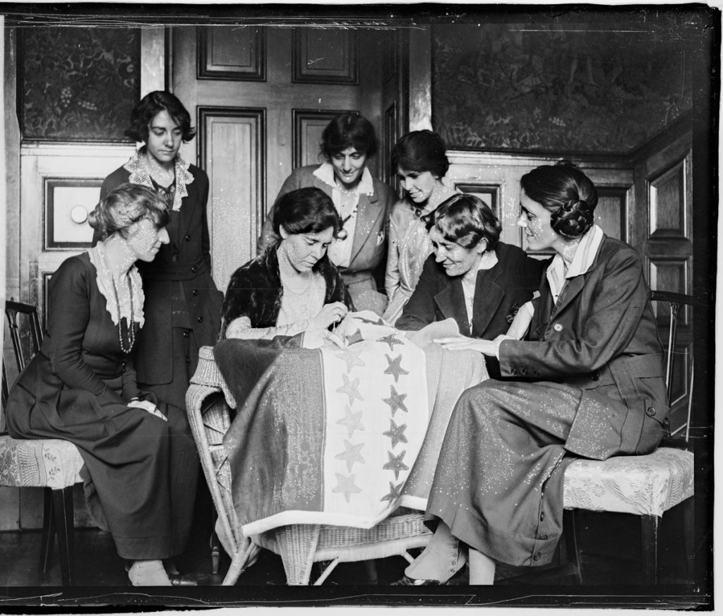 Women gathered around a flag they are sewing (Library of Congress)