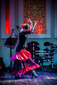 Woman in colorful dress dancing on stage (Courtesy of Aziza Kayumova)