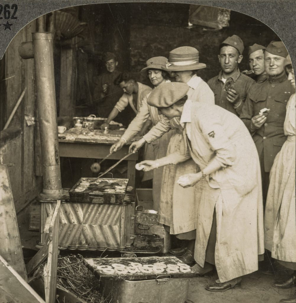 Vintage photo of men and women making and eating doughnuts during WWI (Library of Congress)