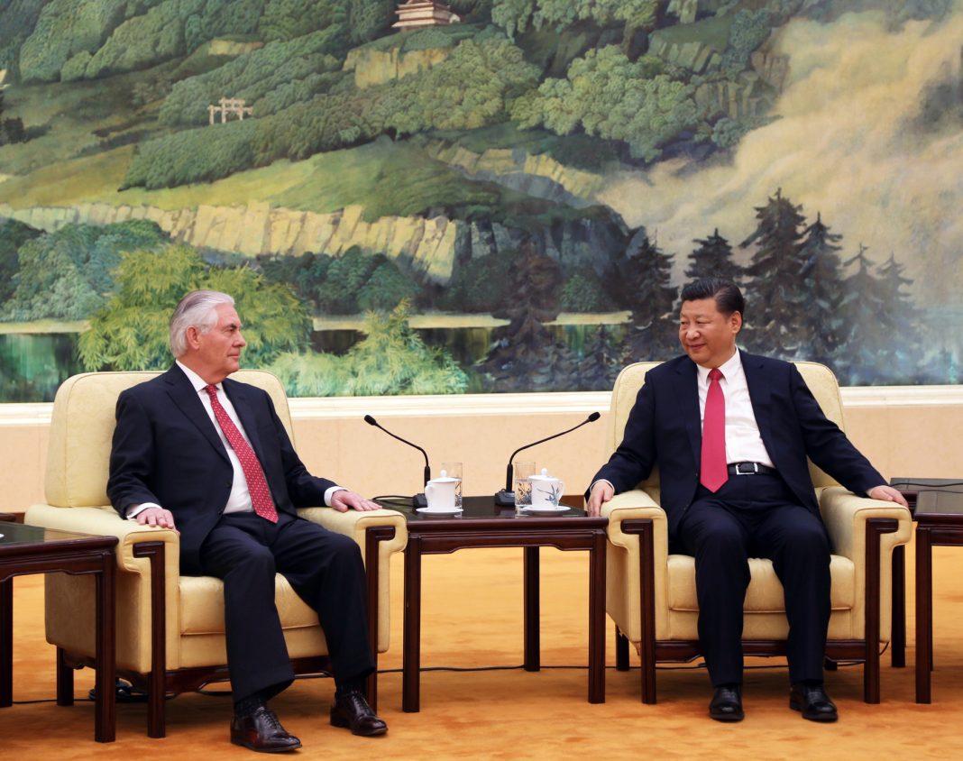 Rex Tillerson y Xi Jinping sentados frente a un mural (Depto. de Estado)