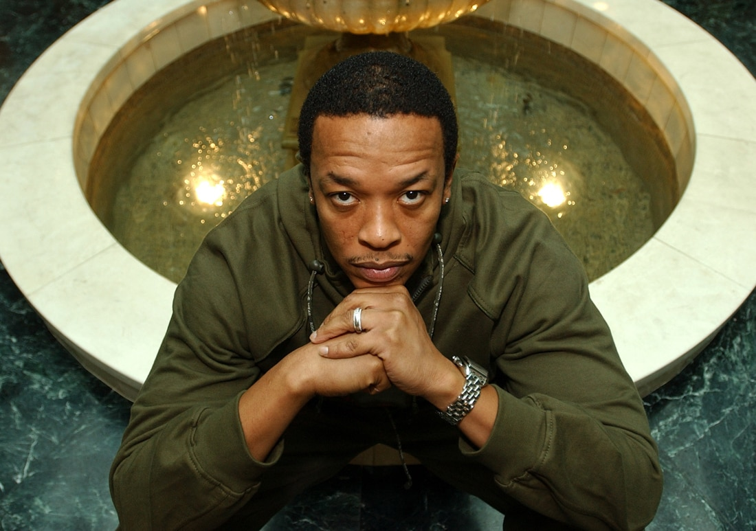 Dr. Dre sitting in front of a fountain (© AP Images)