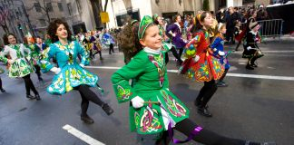 Girls wearing costumes in St. Patrick's Day parade (© AP Images)