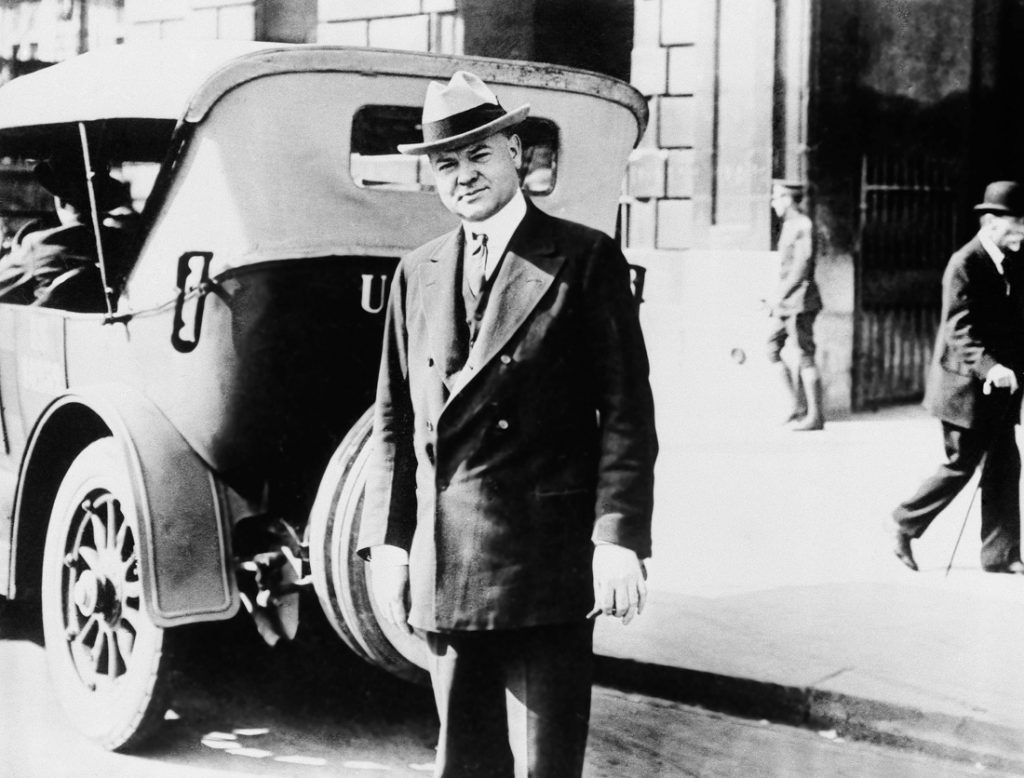 Herbert Hoover standing by car (© AP Images)