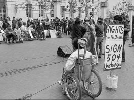 Man in wheelchair at rally with others holding signs (© AP Images)
