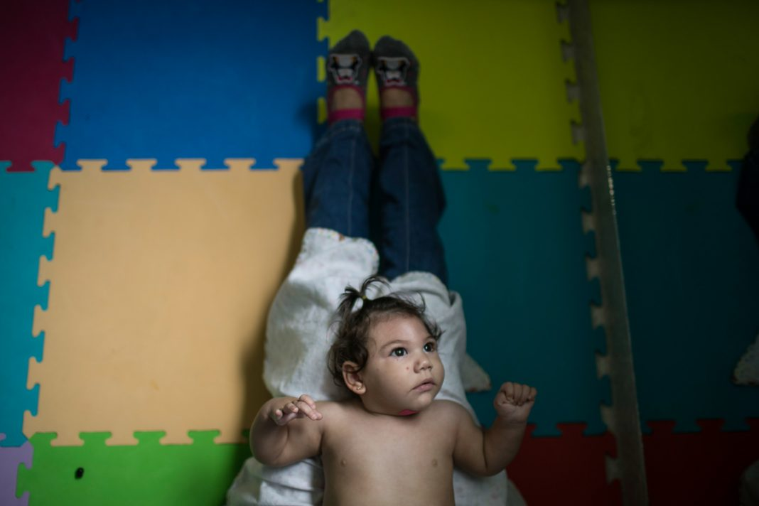 Baby lying on person's legs (© AP Images)