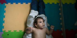 Bebê deitado sobre as pernas de uma pessoa (© AP Images)