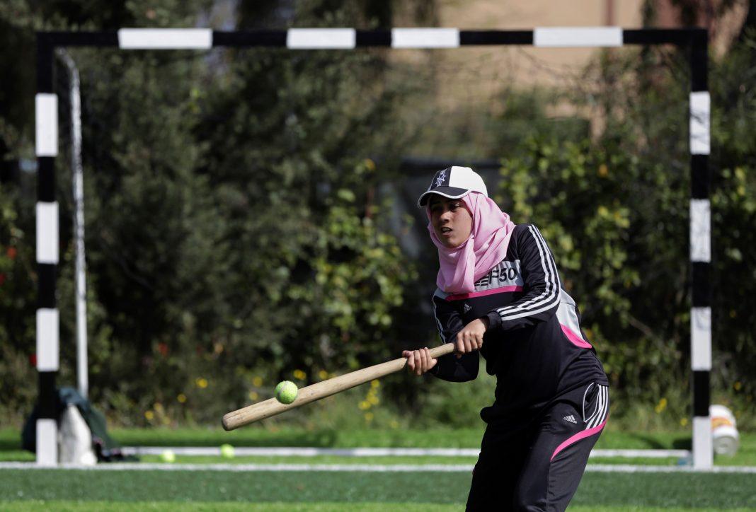 Young woman wearing baseball cap and hijab swinging at a ball with a bat (© AP Images)