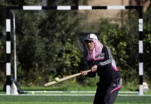 Moça com boné de beisebol e hijab acerta uma bola com um bastão (© AP Images)