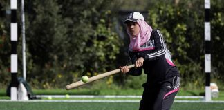 Young woman wearing baseball cap and hijab swinging at a ball with a bat (© AP Images)