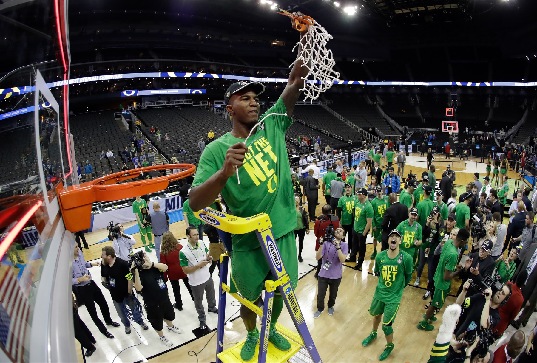 Oregon basketball player holding up basketball net he has just cut from rim. (© Charlie Riedel/AP Images)