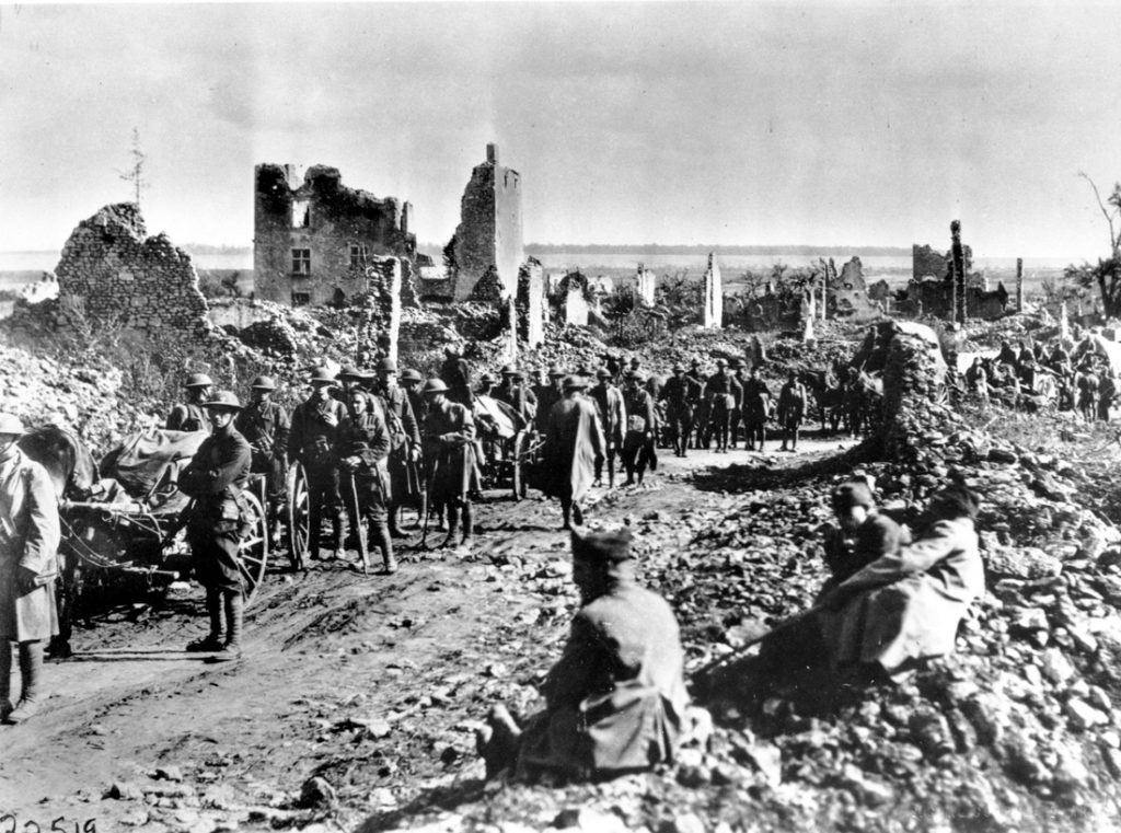 Soldiers marching through destroyed town (© AP Images)