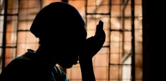 Silhouette of woman with head resting on hand (© AP Images)