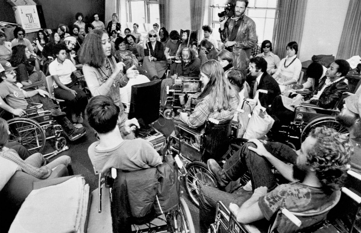 Group of people with disabilities filling room (© AP Images)