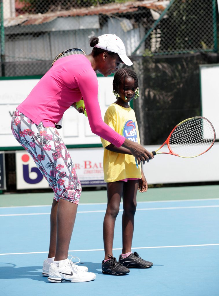 Venus Williams teaching girl to grip racket (© AP Images)