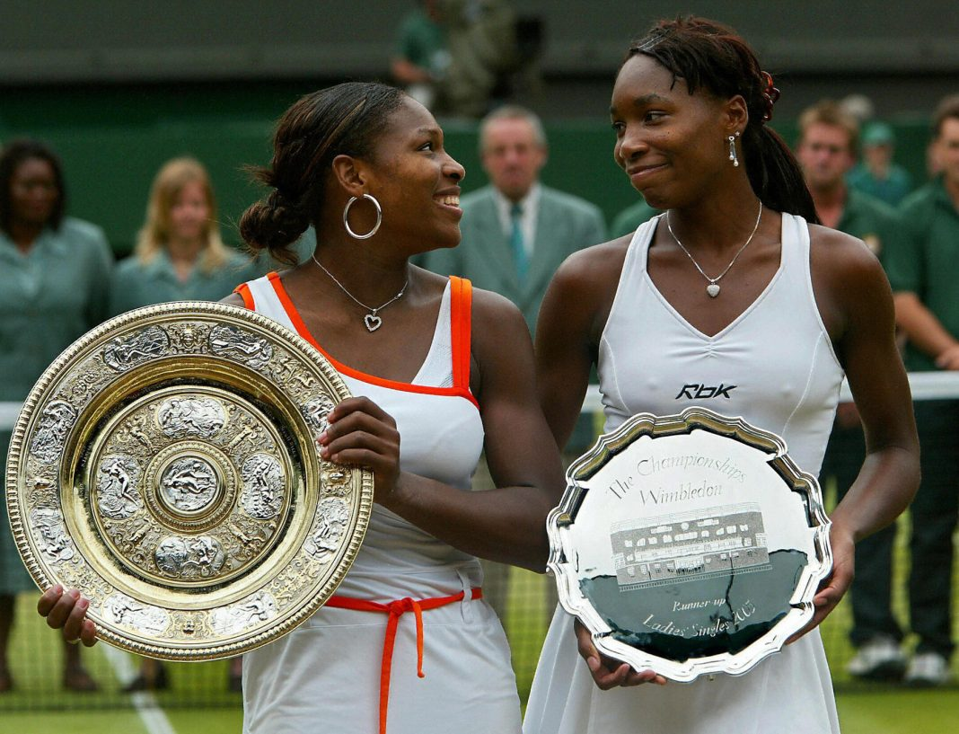 Serena and Venus Williams holding tennis trophies (© Getty Images)