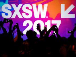 People raising smartphones to capture an SXSW.2017 banner (© Bloomberg via Getty Images)