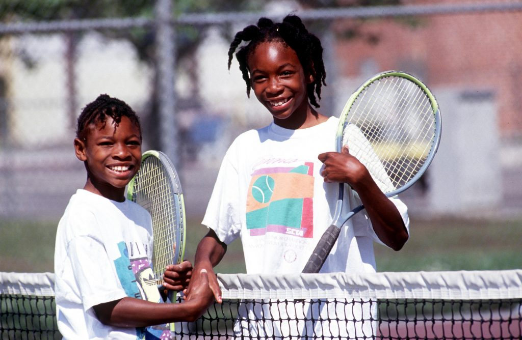 Young Serena and Venus Williams holding rackets and shaking hands at tennis net (© Getty Images)