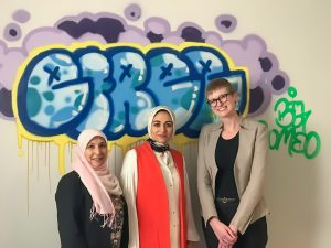 Three women in front of wall with artwork (Courtesy of Zeena Altalib)