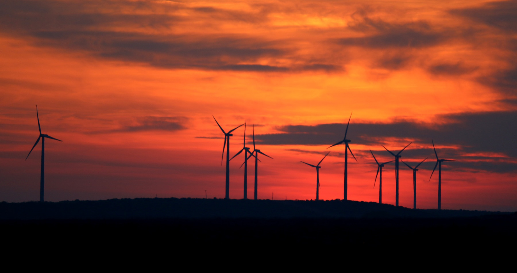 Line of wind turbines on ridge at sunset (ERCOT)