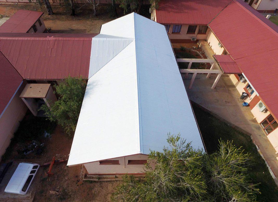 Vue aérienne d'un toit blanc avec des toits rouges autour (PEER Africa)