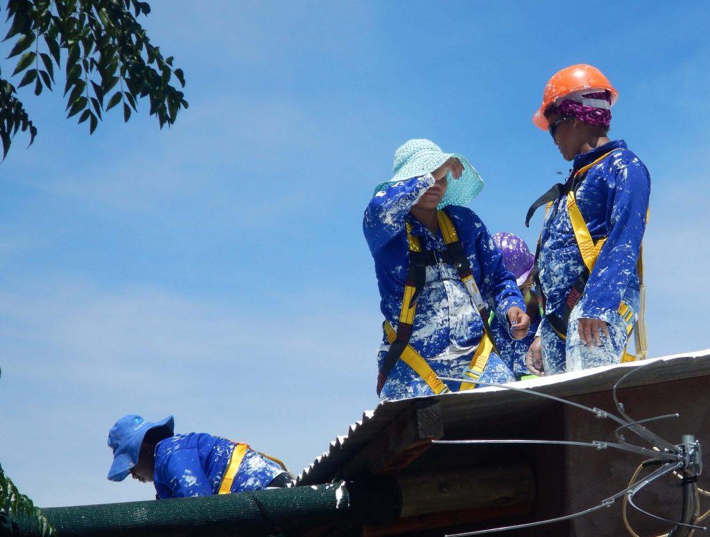 Des ouvriers en bleu de travail sur un toit, un beau ciel bleu en toile de fond (PEER Africa)