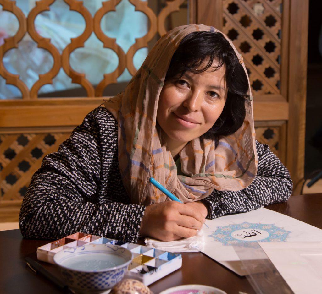 Sughra Hussainy sentada, desenhando (Cortesia: Montanha Turquesa)