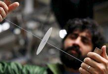 Manu Prakash segura barbante com círculo de papel suspenso nele (Kurt Hickman/Stanford News Service)