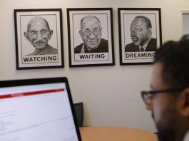 Homem olha para o monitor de um computador; ao lado, retratos de líderes religiosos na parede (Depto. de Estado)