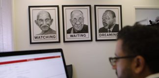 Man looking at computer monitor next to pictures of religious leaders on wall (State Dept.)