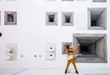 Hombre con traje especial sostiene una guitarra eléctrica, con los brazos en alto, en frente de paredes con altavoces (@everydayastronaut, [astronauta a diario])