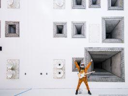 Homem com roupa de astronauta segura guitarra, com braços levantados, em frente de parede com alto-falantes (@everydayastronaut)