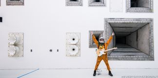 Man in astronaut suit, holding electric guitar, with arms raised, in front of wall of speakers (@everydayastronaut)