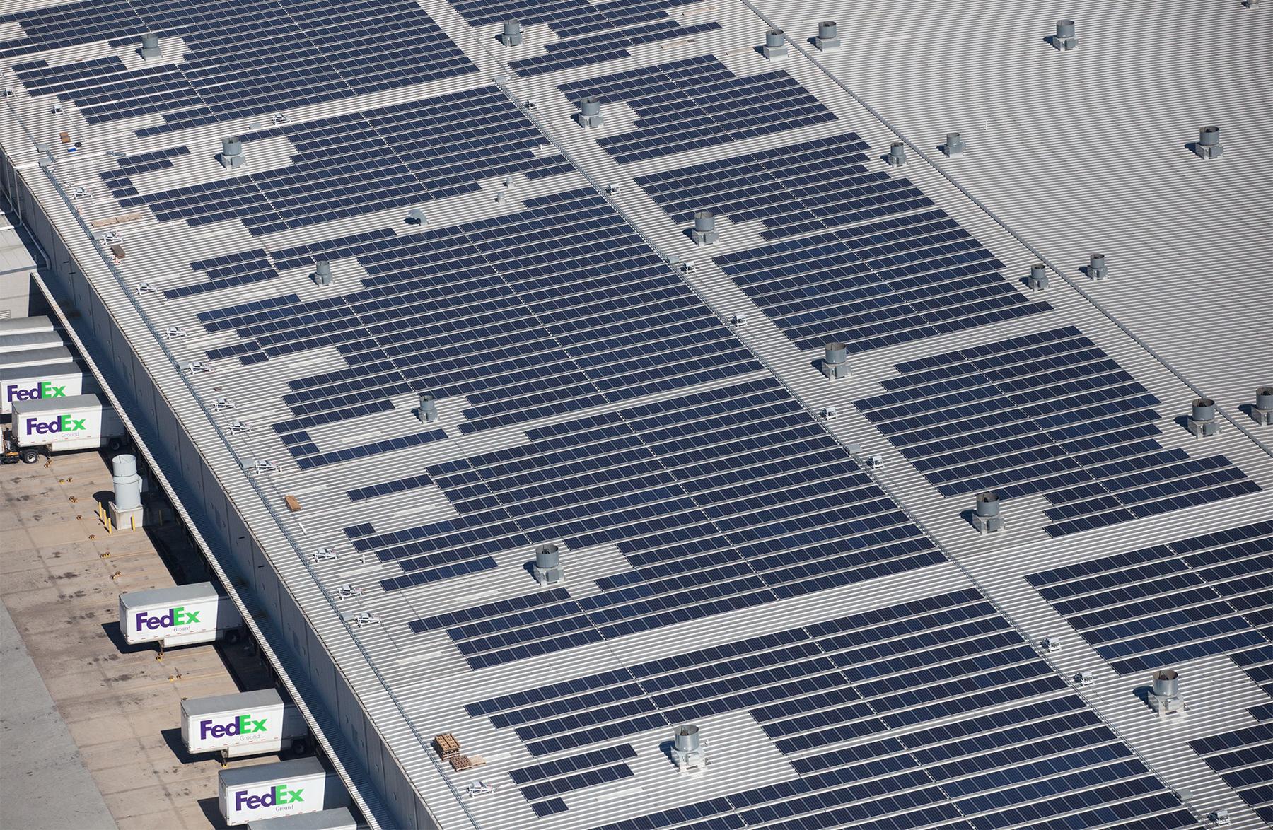 Vista aérea de caminhões de entrega estacionados ao lado de grande edifício com painéis solares cobrindo o telhado (FedEx)