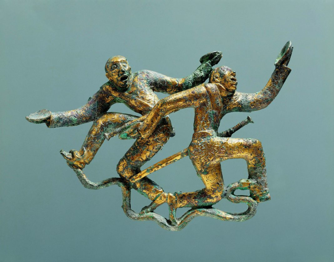 Two green-and-gold figures with outstretched limbs and a snake underfoot (Courtesy of Yunnan Provincial Museum, Kunming)