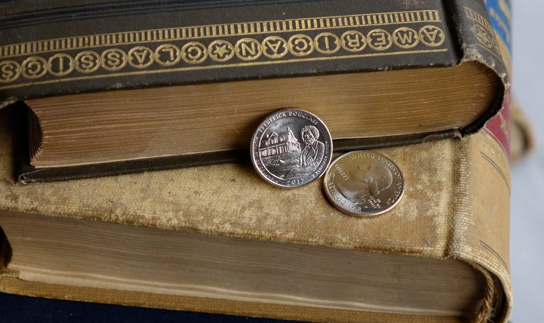 Two Frederick Douglass quarters resting on old books (U.S. Mint)