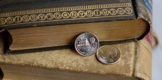 Dos monedas de 25 centavos de Frederick Douglass sobre libros antiguos (U.S. Mint)
