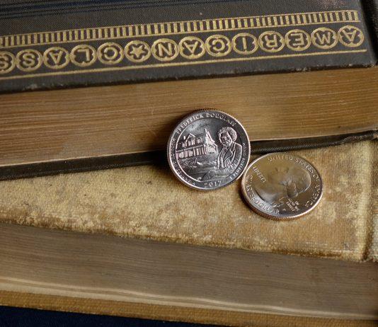 Duas moedas de um quarto de dólar sobre livros antigos (Casa da Moeda dos EUA)