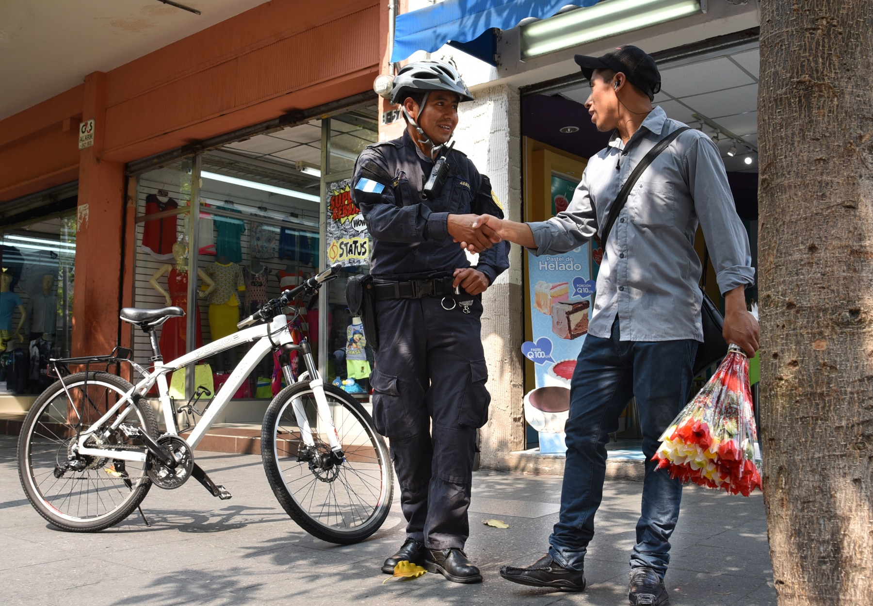 Policial ao lado de bicicleta aperta a mão de homem (Embaixada dos EUA na Guatemala)