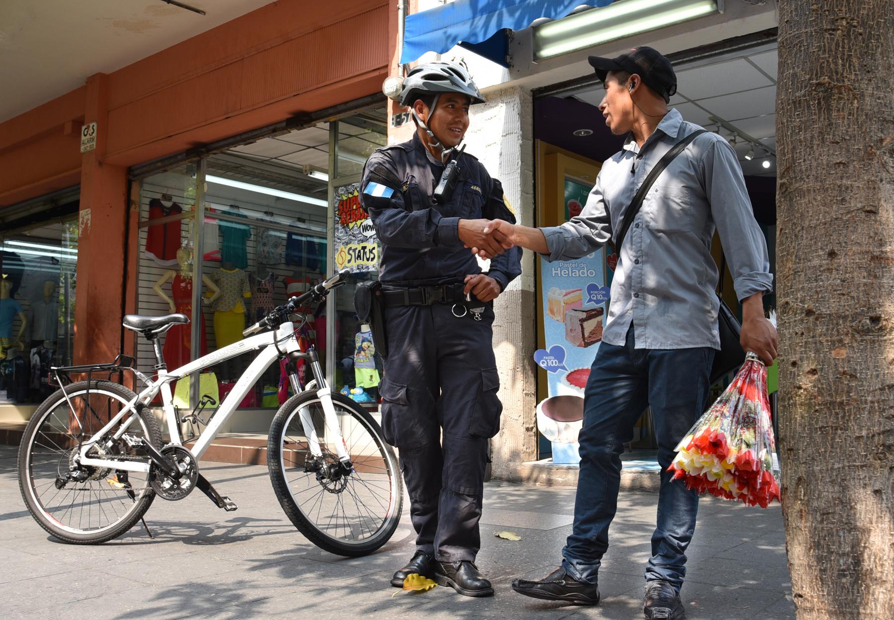 Police officer standing near bike and shaking man's hand (U.S. Embassy Guatemala)