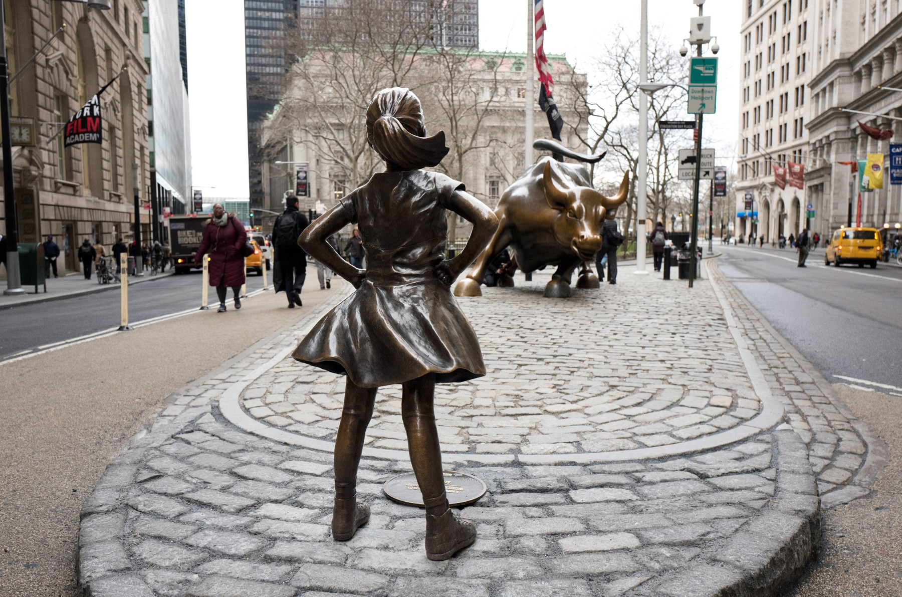 Girl statue standing in front of bull statue between two city streets (© AP Images)