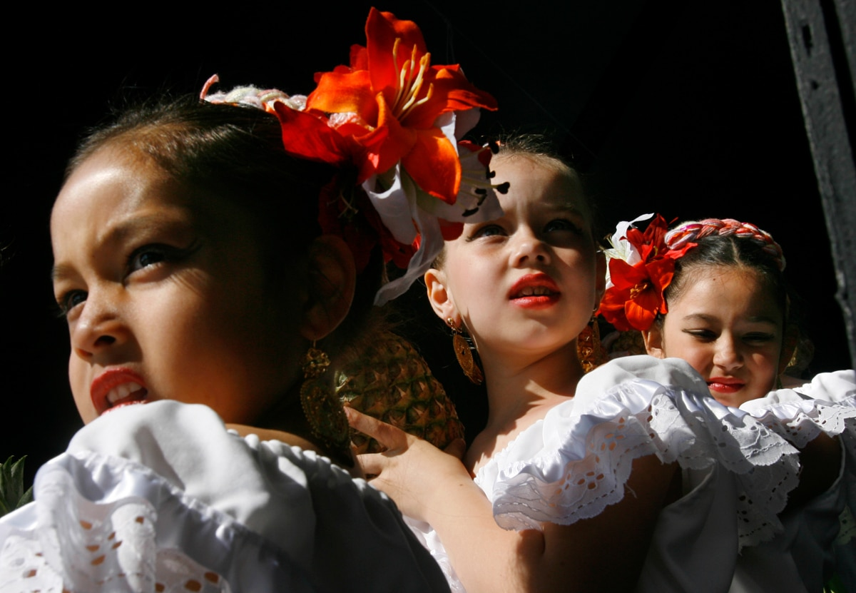 Three young girls in dancing costumes (© AP Images)