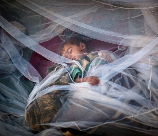 Boy under mosquito net (© AP Images)