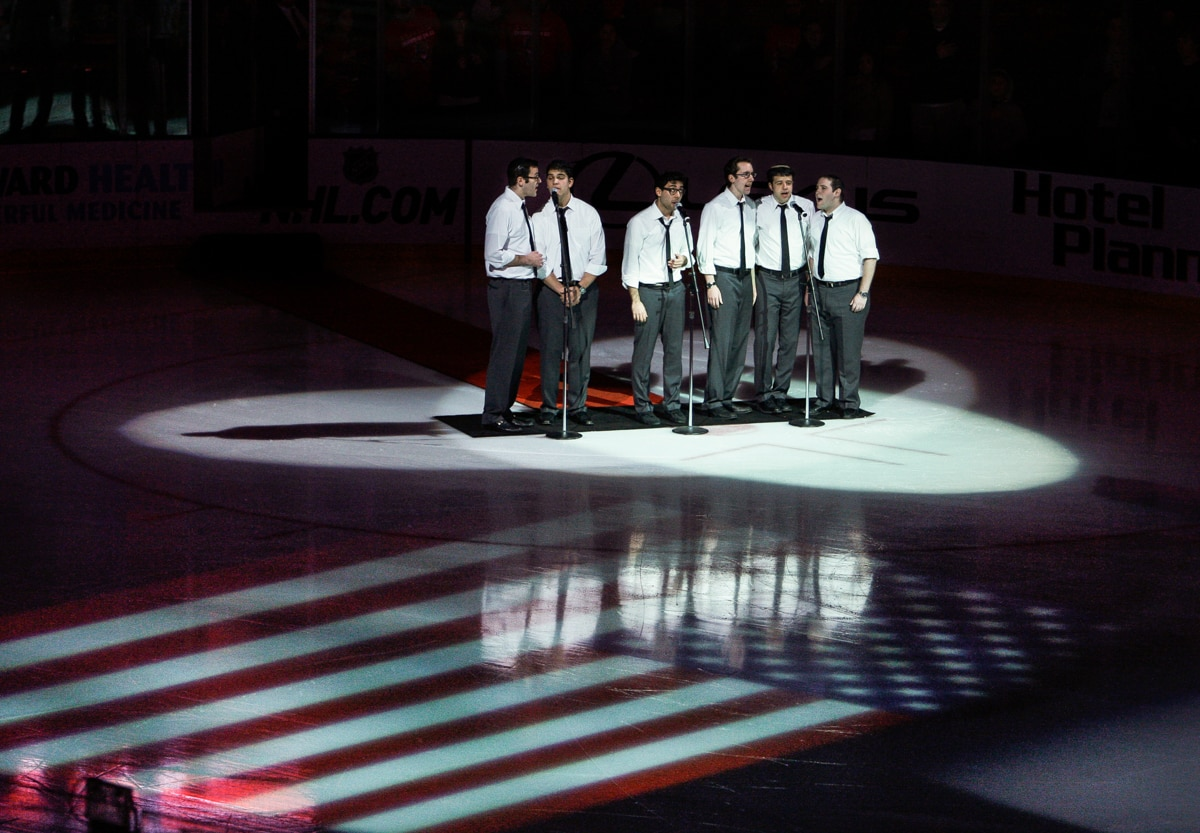 Group of men standing on ice and singing (© AP Images)