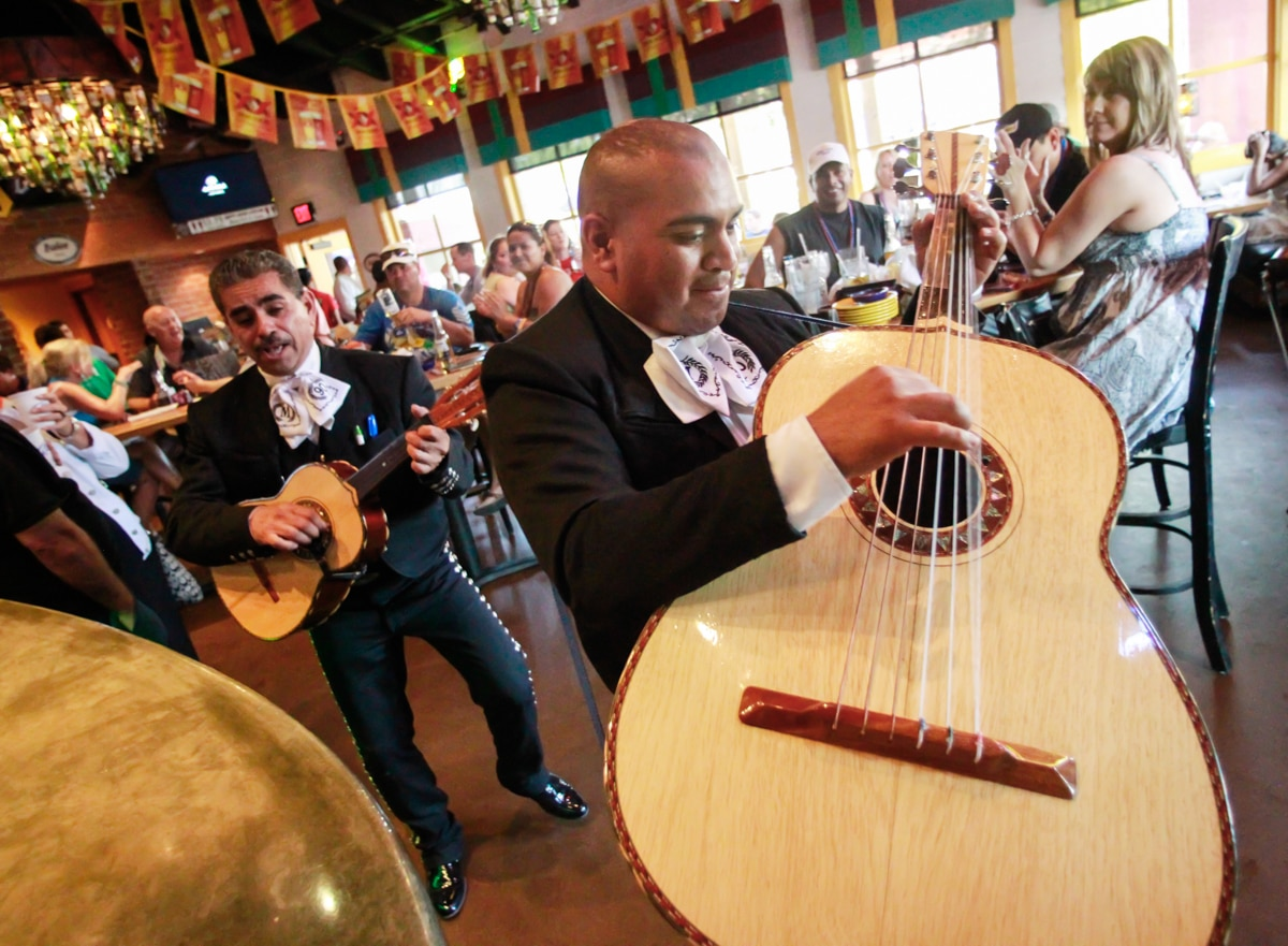 Close-up of guitarist in a mariachi band performing in a restaurant (© AP Images)
