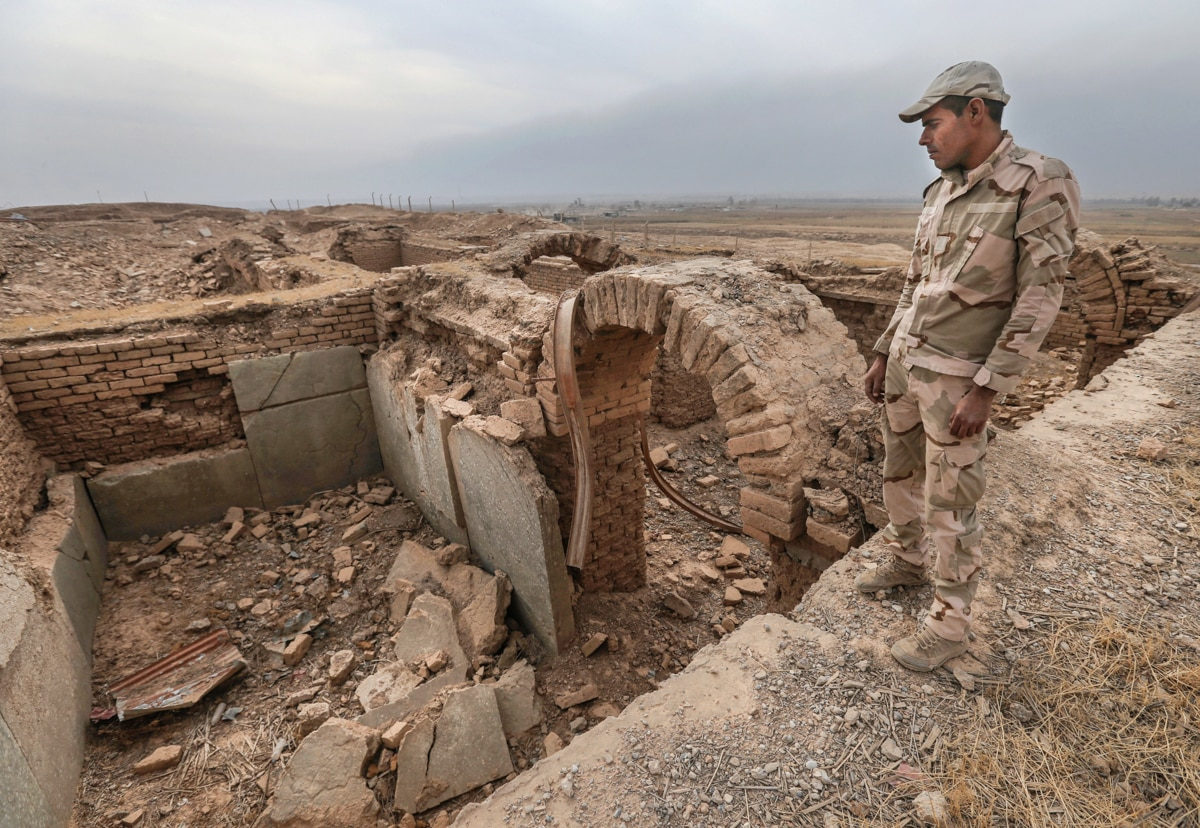 Soldier standing over damaged ruins of ancient building site (© AP Images)
