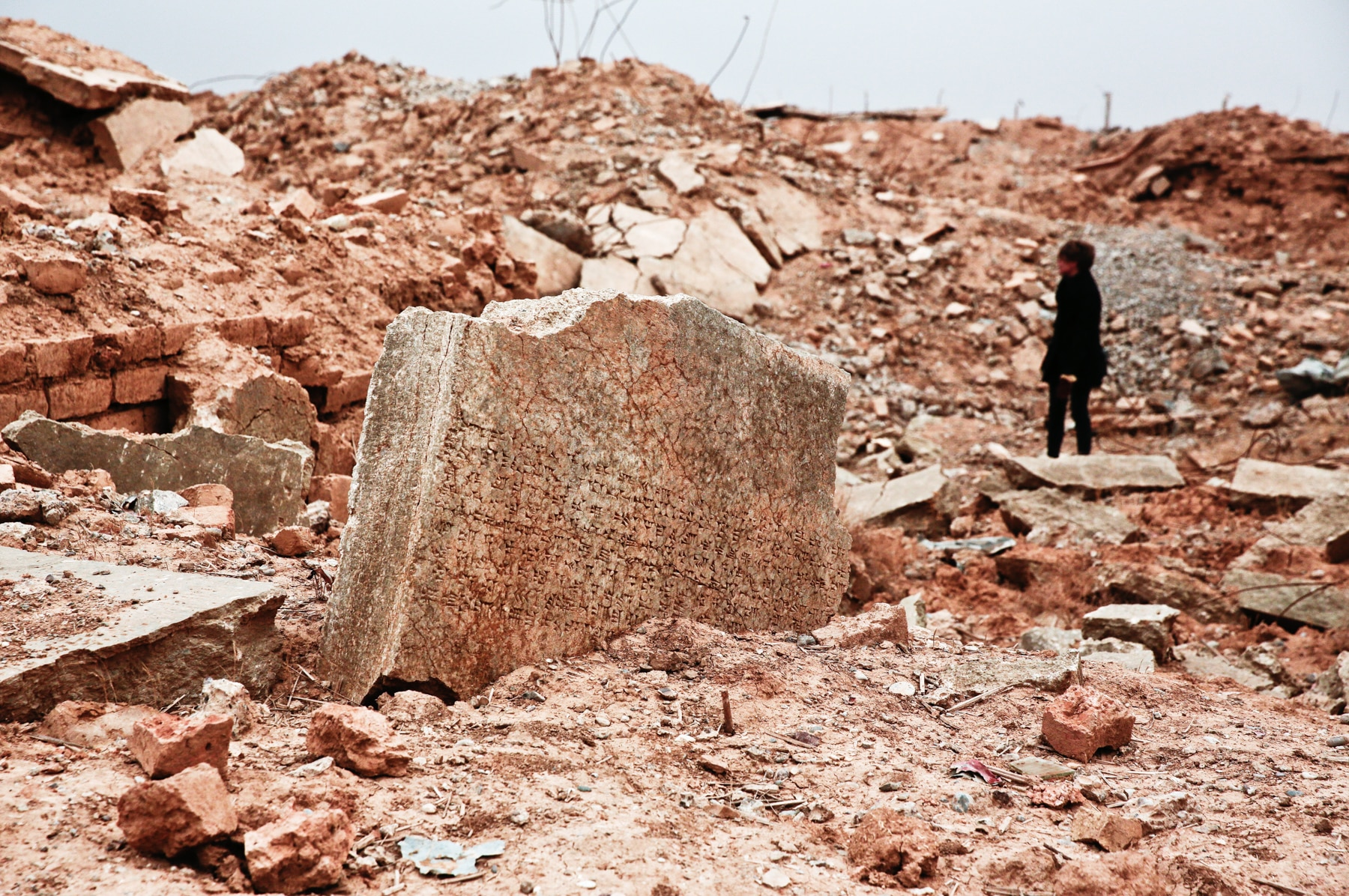 Destroyed monuments with person in background (© AP Images)
